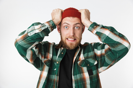 Portrait of uptight man wearing hat and plaid shirt screaming and grabbing head while standing isolated over white background