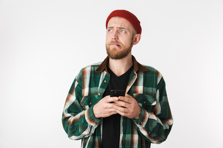 Portrait of displeased guy wearing hat and plaid shirt using mobile phone while standing isolated over white background