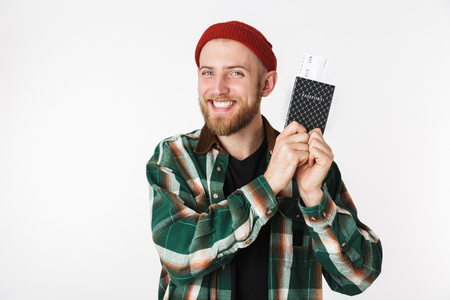 Portrait of satisfied guy wearing hat and plaid shirt holding passport and travel tickets while standing isolated over white background