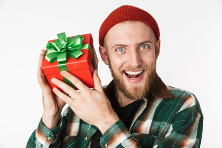 Portrait of joyful guy wearing hat and plaid shirt holding gift box while standing isolated over white background