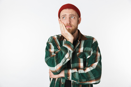 Portrait of displeased man wearing hat and plaid shirt grabbing his face while standing isolated over white background