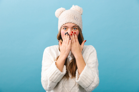 Shocked young girl wearing winter clothes standing isolated over blue background, cover face