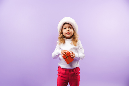 Cheerful little girl holding Christmas present box isolated over violet background