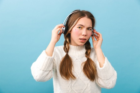 Confused young girl wearing winter clothes standing isolated over blue background, listening to music with headphones