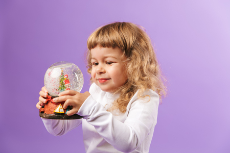 Pretty little girl holding christmas globe isolated over violet background
