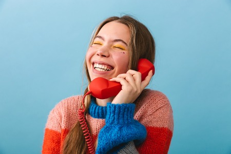 Excited young girl wearing winter clothes standing isolated over blue background, talking on a landline phone