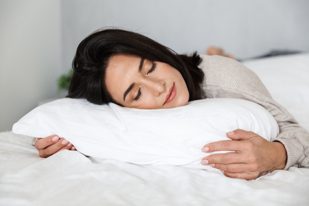 Photo of adult woman 30s sleeping while lying in bed with white linen at home