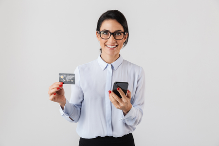 Image of smart office woman wearing eyeglasses holding mobile phone and credit card isolated over white background