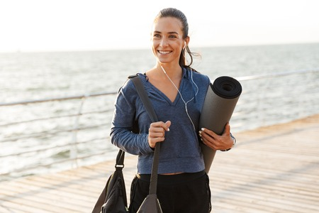 Smiling sportswoman walking at the beach, carrying fitness mat
