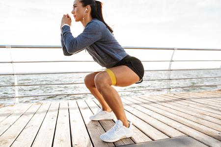 Skoncentrowana sportsmenka wykonująca ćwiczenia z gumką na plaży Zdjęcie Seryjne