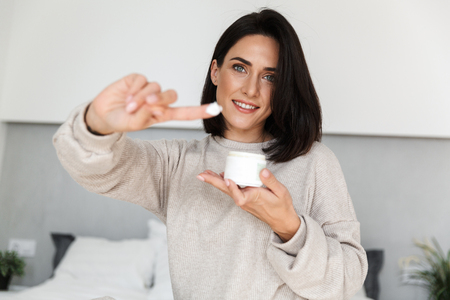 Image of attractive woman 30s holding jar with face cream in modern bright room