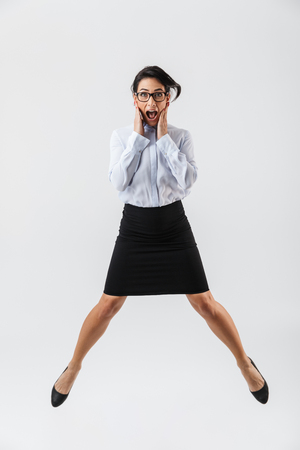 Full length portrait of a pretty businesswoman jumping isolated over white background, celebrating success