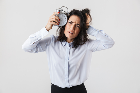 Upset businesswoman smartly dressed standing isolated over white background, showing alarm clock