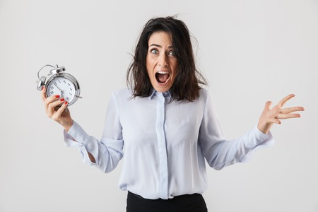 Shocked businesswoman smartly dressed standing isolated over white background, showing alarm clock, screaming