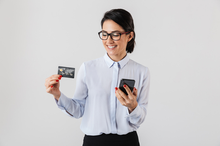 Image of confident office woman wearing eyeglasses holding mobile phone and credit card isolated over white background Stock Photo
