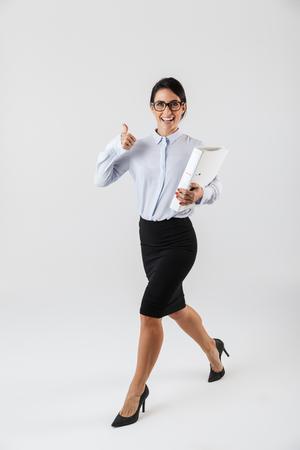 Full length photo of european businesswoman wearing eyeglasses holding paper folder in the office isolated over white background