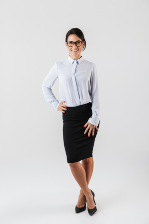 Full length photo of adult businesswoman wearing eyeglasses standing in the office isolated over white background