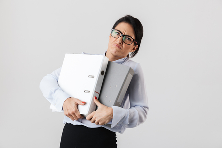 Photo of businesslike female worker wearing eyeglasses holding paper folders in the office isolated over white background