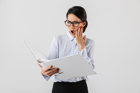Shocked businesswoman smartly dressed standing isolated over white background, looking through documents Imagens