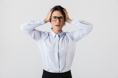Image of upset secretary woman wearing eyeglasses standing in the office isolated over white background