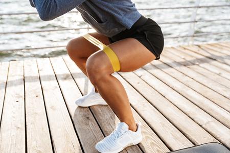 Primo piano di una sportiva che fa esercizi con un elastico in spiaggia