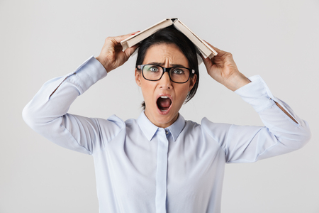 Photo of funny female worker wearing eyeglasses holding book on head in the office isolated over white background
