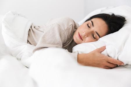 Foto einer Frau mittleren Alters 30 schläft, während sie zu Hause mit weißer Bettwäsche im Bett liegt