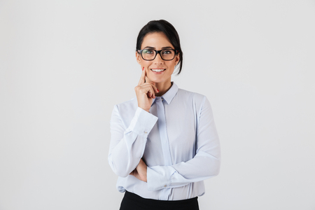 Photo of successful businesswoman wearing eyeglasses standing in the office isolated over white background