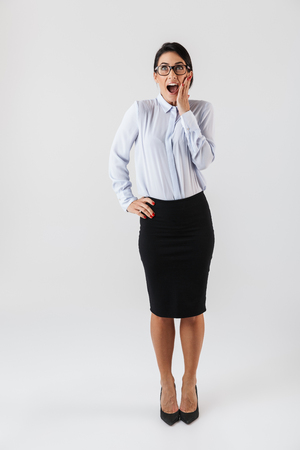 Full length photo of businesslike woman wearing eyeglasses standing in the office isolated over white background Stock Photo