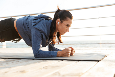 Concentrated sportswoman doing plank exercises on a fitness mat at the beach