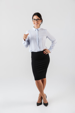 Full length photo of attractive businesswoman wearing eyeglasses standing in the office isolated over white background