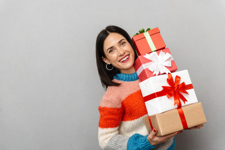Photo of excited woman 30s holding bunch of gift boxes while standing isolated over gray background