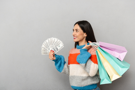 Photo of successful woman 30s holding bunch of money and shopping bags isolated over gray background Stock Photo