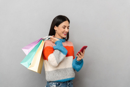 Portrait of beautiful woman 30s carrying colorful paper shopping bags and holding cell phone isolated over gray background