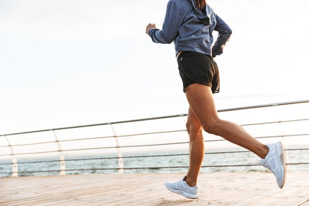 Cropped image of a young sports fitness woman running at the beach outdoors.