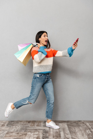 Portrait of emotional woman 30s running with colorful paper shopping bags and cell phone in hands isolated over gray background Stock Photo