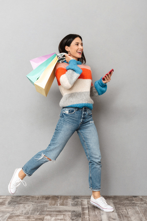 Portrait of brunette woman 30s running with colorful paper shopping bags and cell phone in hands isolated over gray background