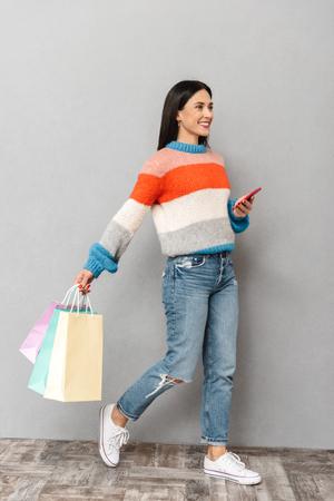 Retrato de mujer alegre de 30 años caminando con coloridas bolsas de papel y teléfono celular en manos aisladas sobre fondo gris Foto de archivo