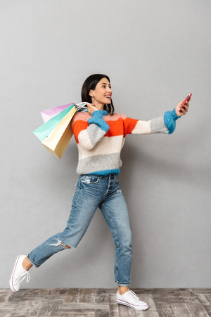 Portrait of smiling woman 30s running with colorful paper shopping bags and cell phone in hands isolated over gray background Stock Photo