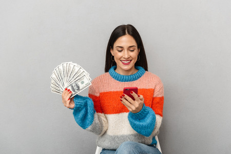 Photo of positive woman 30s holding bunch of money and smartphone isolated over gray background