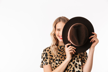 Image of a beautiful young woman covering face with hat isolated over white wall background.