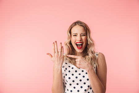 Beautiful excited young blonde woman wearing dress standing isolated over pink background, showing engagement ring on her finger