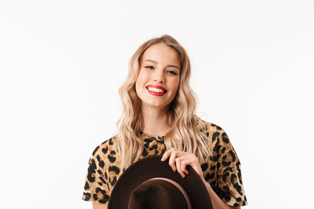 Image of a beautiful happy excited young woman with hat isolated over white wall background.