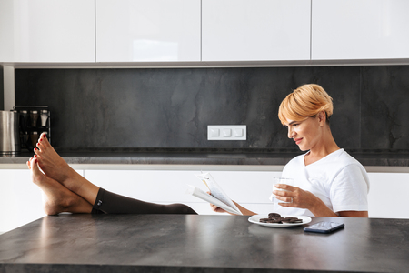 Pretty woman reading a newspaper while sitting at the kitchen table, drinking milk from a glass, eating cookies