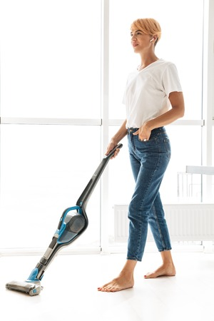 Attractive young woman vacuuming at the living room at home