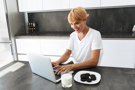 Pretty woman using laptop computer while sitting at the kitchen table, drinking milk from a glass, eating cookies
