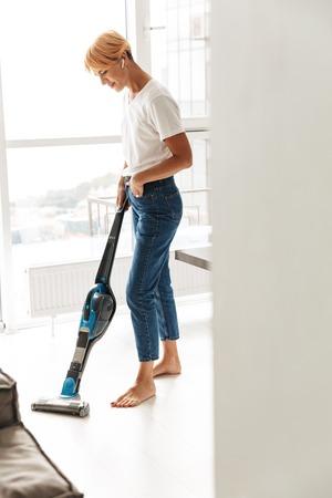Mujer joven atractiva pasar la aspiradora en la sala de estar en casa