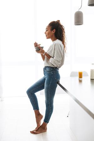 Image of skinny african american woman eating corn flakes with milk on breakfast in stylish kitchen