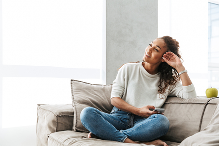 Photo of happy african american woman using cell phone while sitting on couch in bright apartment