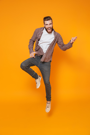 Full length portrait of a cheerful young man wearing casual clothes isolated over yellow background, jump
